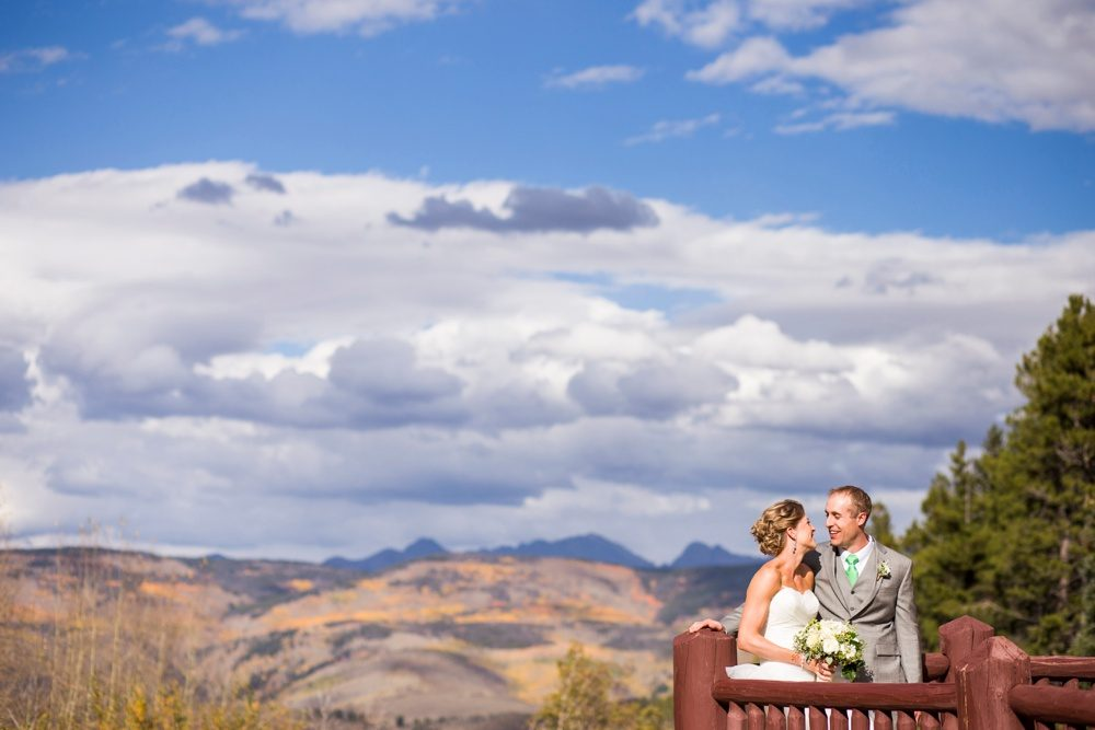 A bride and groom share a private moment on the balcony at Beaver Creek Resort on gorgeous fall afternoon in the Colorado mountains.