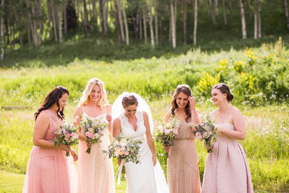 A bride laughs with her bridesmaids dressed in pastel pink dresses on a gorgeous day in the Colorado mountains.