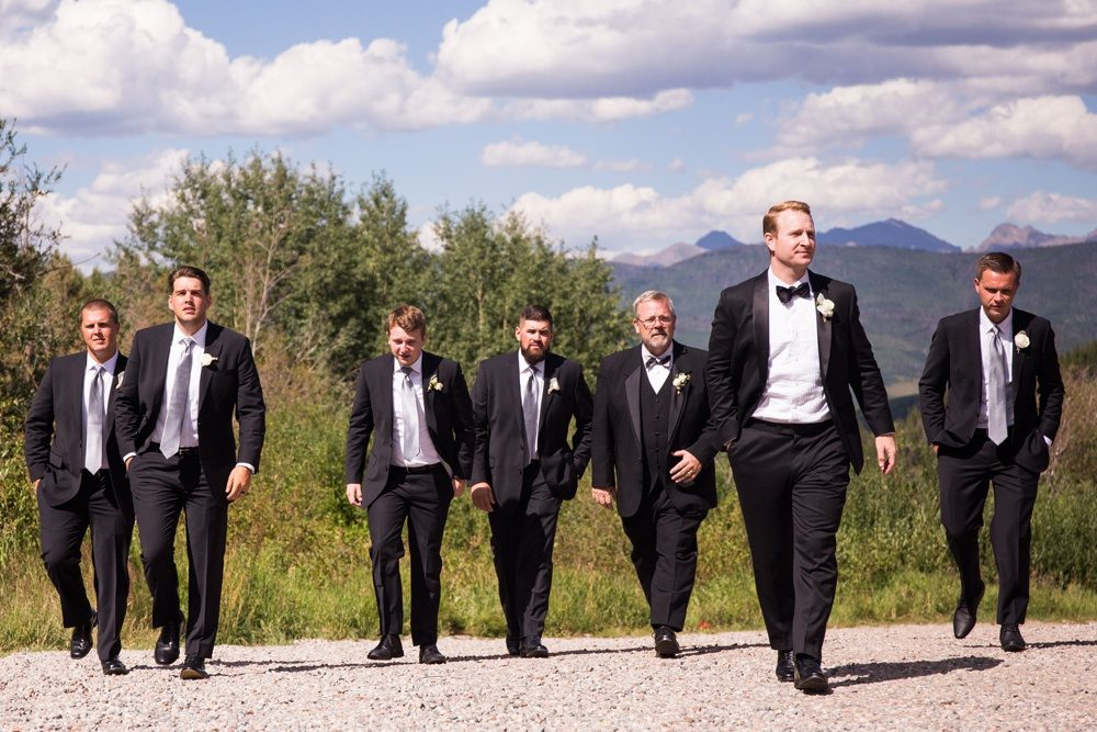 groom and groomsmen wearing black tuxedos walking up the gravel driveway at beano's cabin in beaver creek, colorado