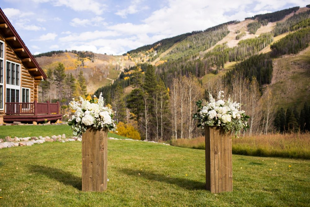 Wedding decor made of white flowers on wood pedestals frame the alter at a mountain wedding venue in Colorado.