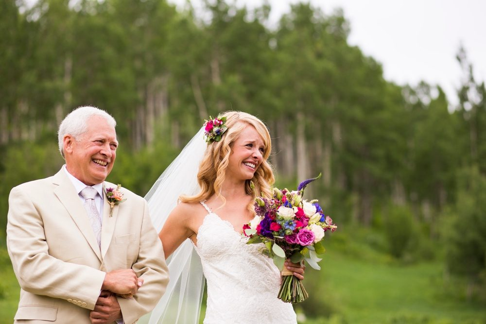 A bride and her father fight back tears as they walk down the aisle.