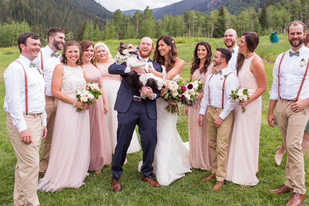 A wedding party gathers for a photo and all eyes and smiles are on the flower girl that is the bride and groom's dog.