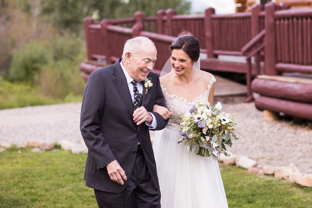 A bride and her grandfather share a sweet glance as they begin the walk down the aisle to the ceremony.