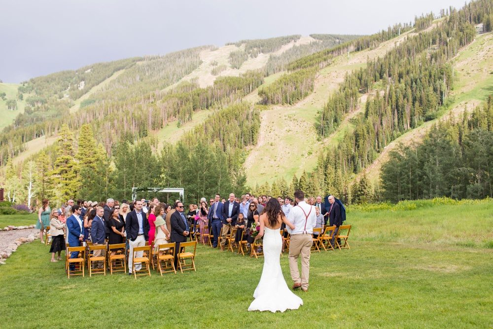 A bride and her brother walk down the aisle in Beaver Creek, Colorado surrounded by the beauty of the rocky mountains in the distance.