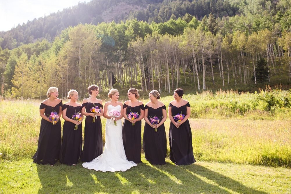 A bride gathers outside her wedding reception with her bridesmaids for a photo.