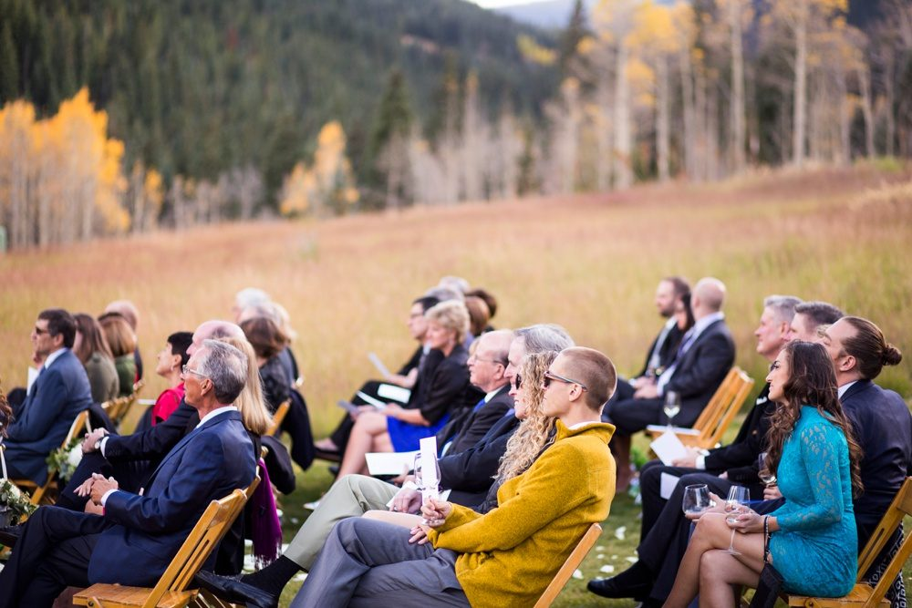 Subtle smiles convey quiet excitement as friends and family watch an outdoor wedding ceremony