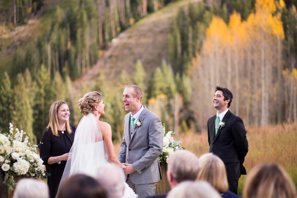 bride and groom laughing as they exchange vows at their outdoor ceremony in colorado, the ski slopes of beaver creek in the background