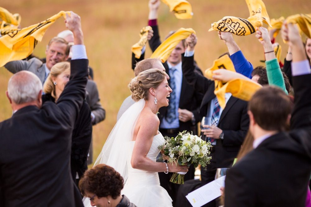 family and friends excitedly wave towels as the bride and groom exit the aisle of their wedding ceremony