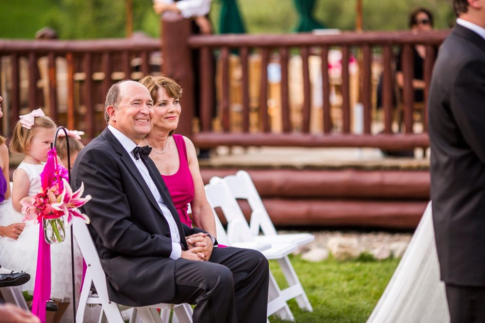 mother and father of the bride watch proudly as their daughter reads vows at her wedding ceremony