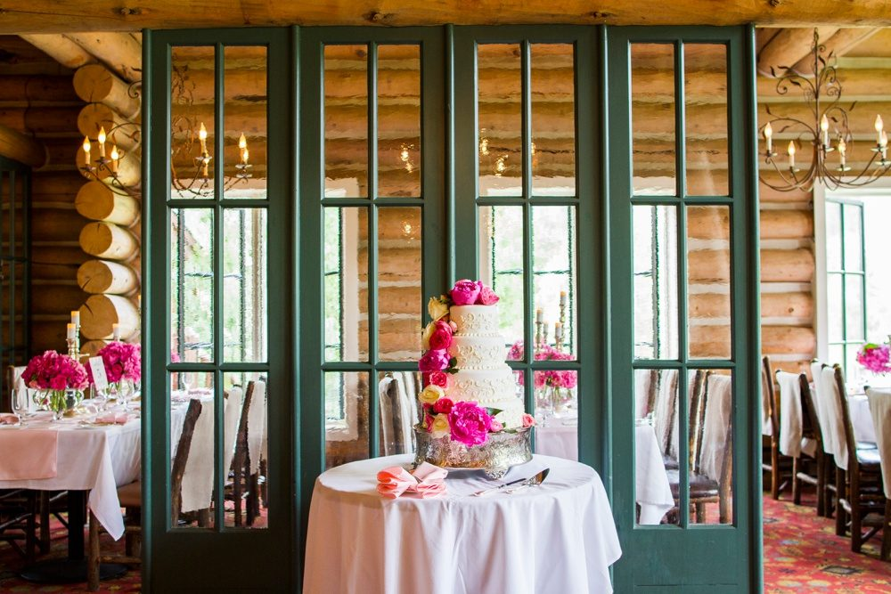 four tier wedding cake decorated with fuchsia and white flowers inside a colorado log cabin wedding venue