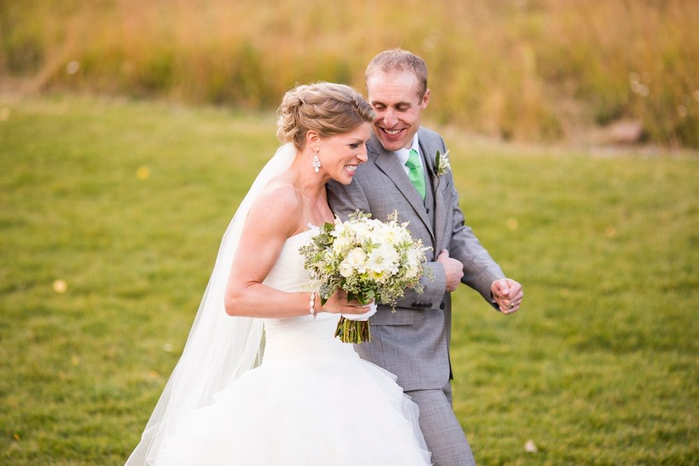 a bride and groom excitedly exit the aisle of their outdoor wedding ceremony