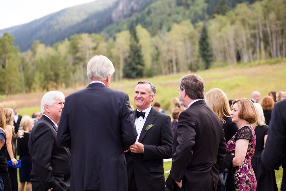 wedding guests mingle and socialize on the lawn at beano's cabin surrounded by aspen trees