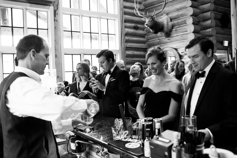 guests gather at the bar in beano's cabin during cocktail hour at a wedding