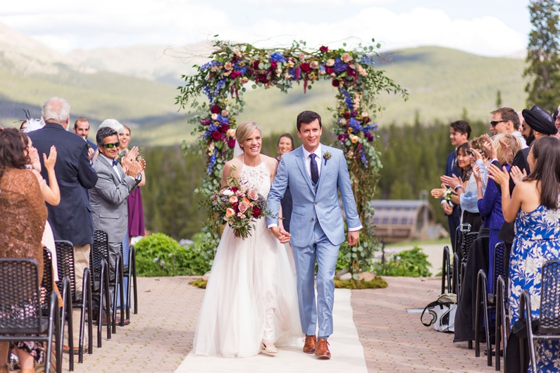 A joyful bride and groom exit the aisle of their wedding ceremony.