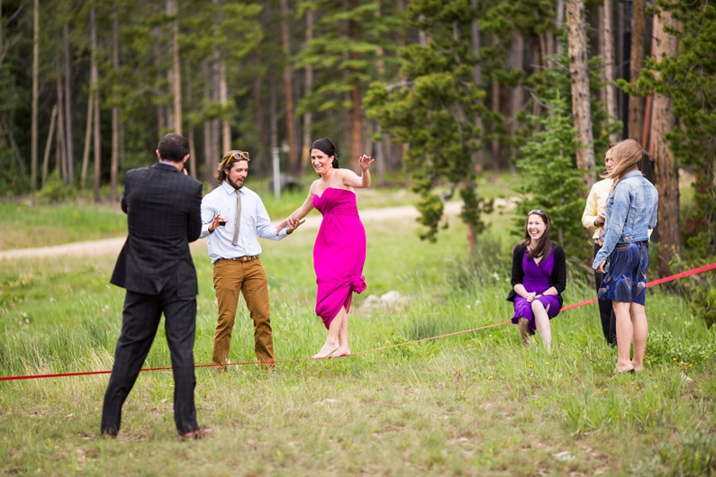 Wedding guests try out a slack line during cocktail hour at a wedding in Breckenridge.