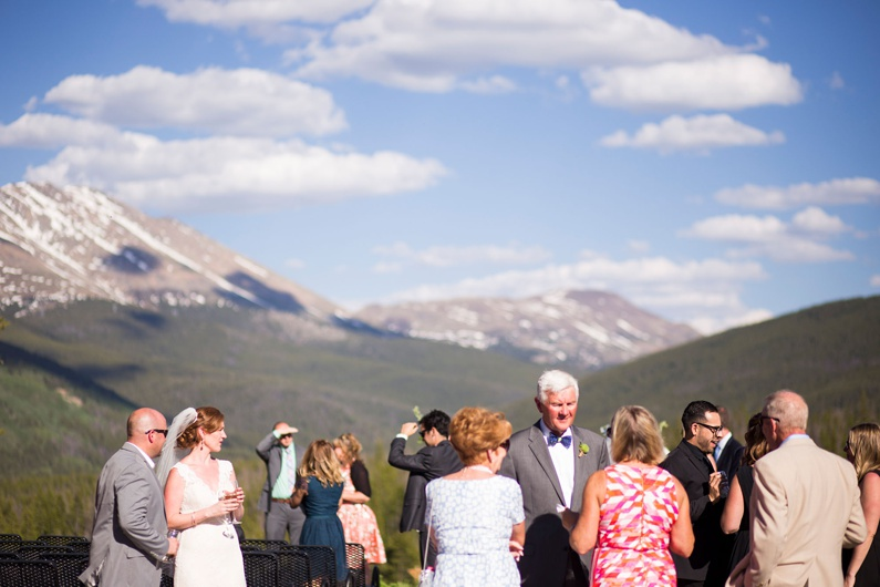 Wedding guests enjoy cocktail hour on the patio at Ten Mile Station surrounded by snow covered peaks.
