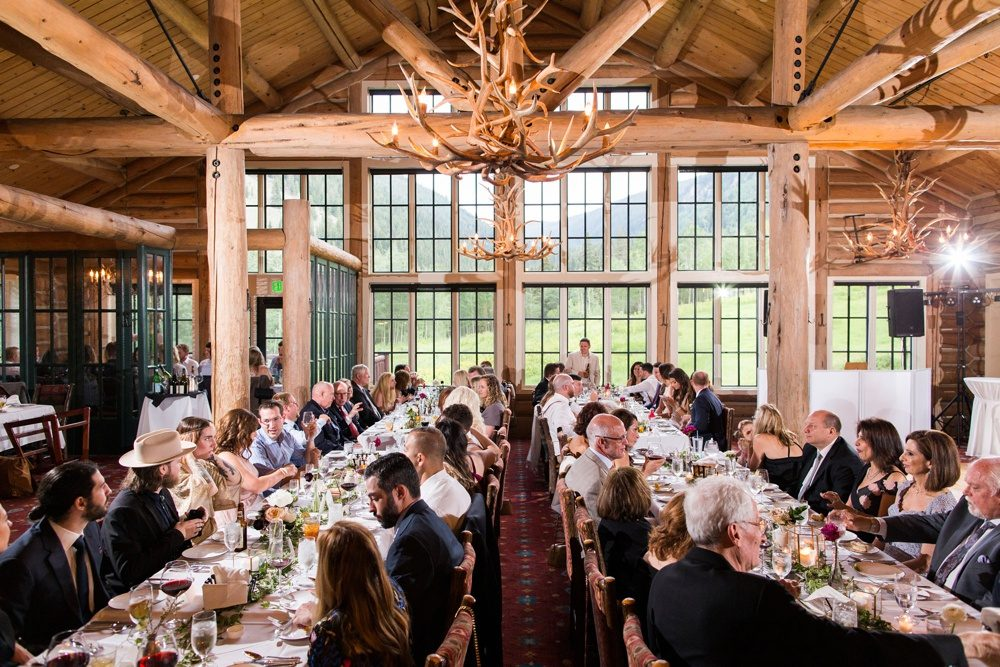 wedding guests seated at long tables as they mingle before dinner inside beano's cabin