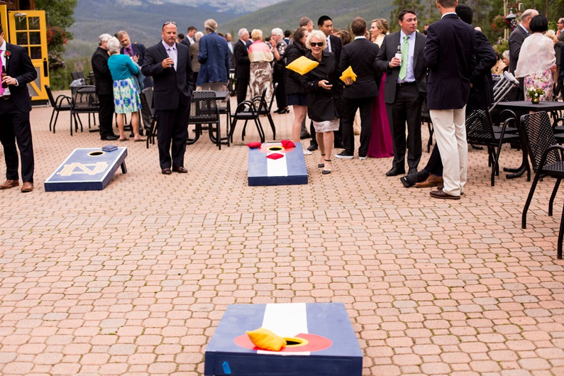 Wedding guests play corn hole on the patio at Ten Mile Station.