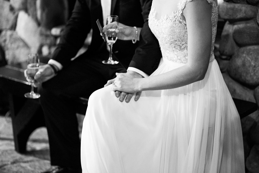 close up black and white photo of a bride and groom holding hands and champagne as the father of the bride offers a toast