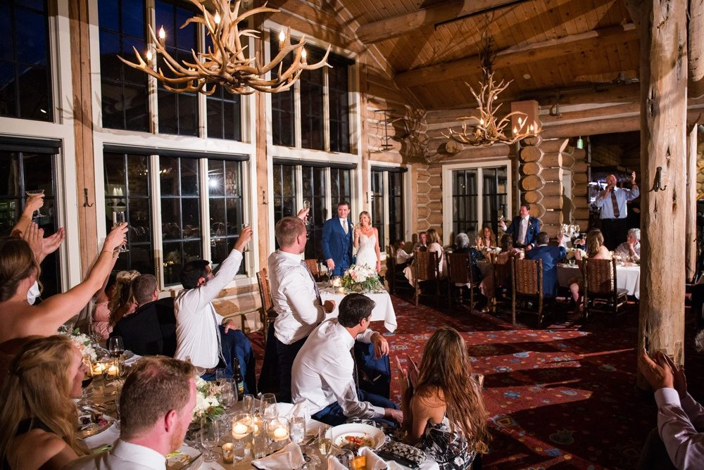 wedding guests cheer on the bride and groom as their reception kicks off in the luxury mountain lodge that is beano's cabin
