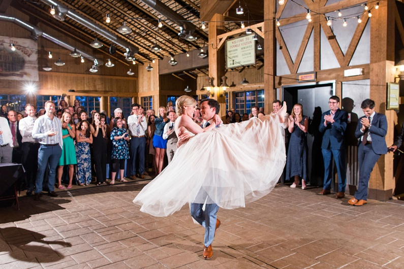 A Groom lifts and spins his bride around the dance floor for their first dance as husband and wife.