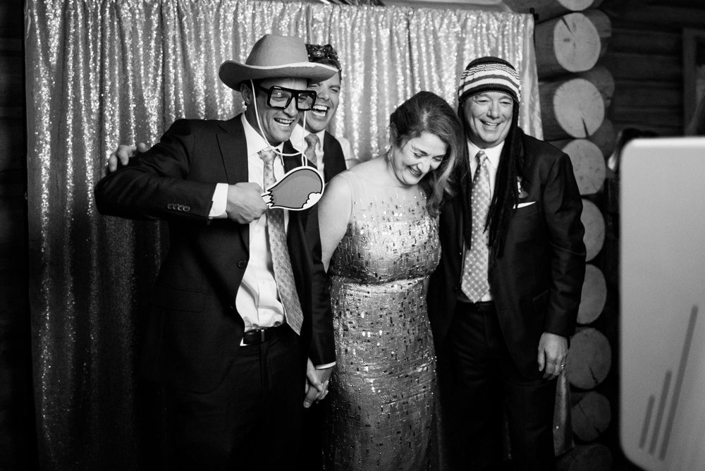 wedding guests laughing and wearing props while getting their photo taken in a photo booth
