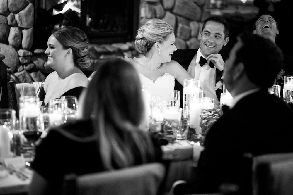 bride and groom laughing as they're toasted at their wedding reception