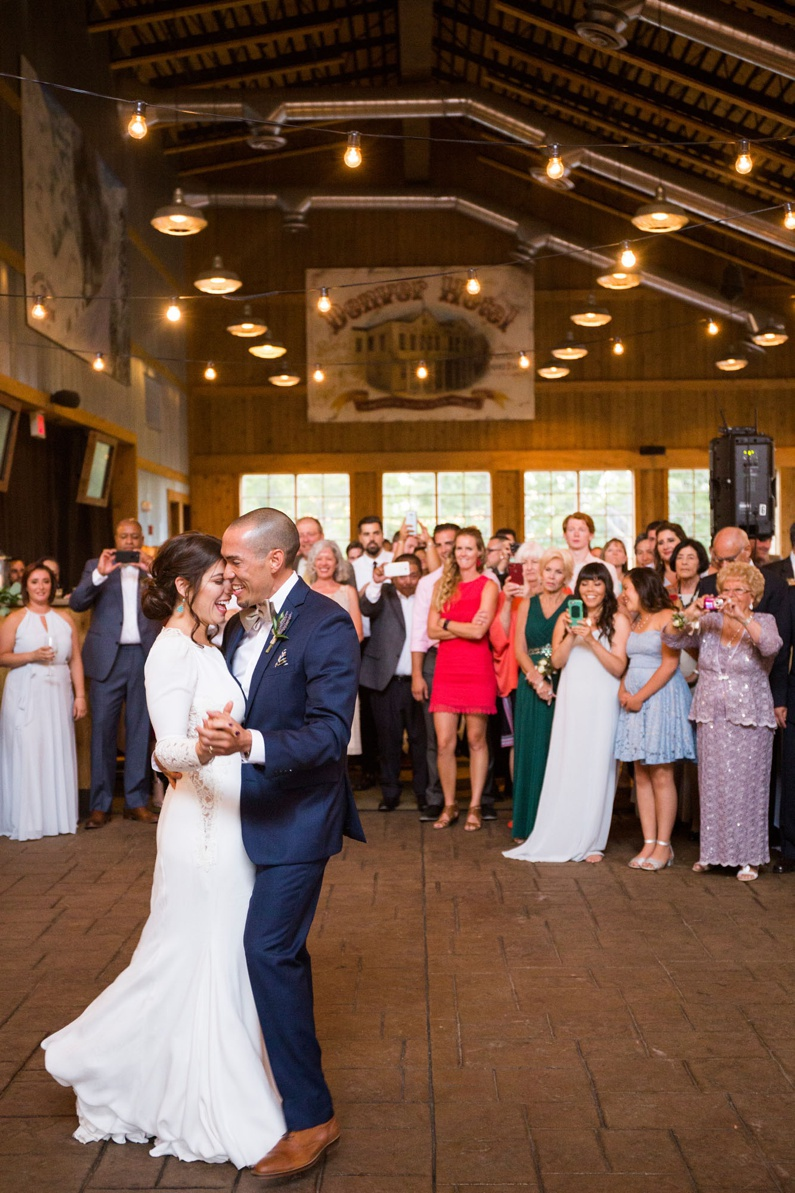 Bride and groom share their first dance as husband and wife while their family and friends watch in the distance.