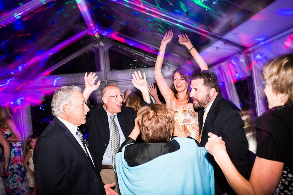 guests dance at a wedding reception inside a clear tent