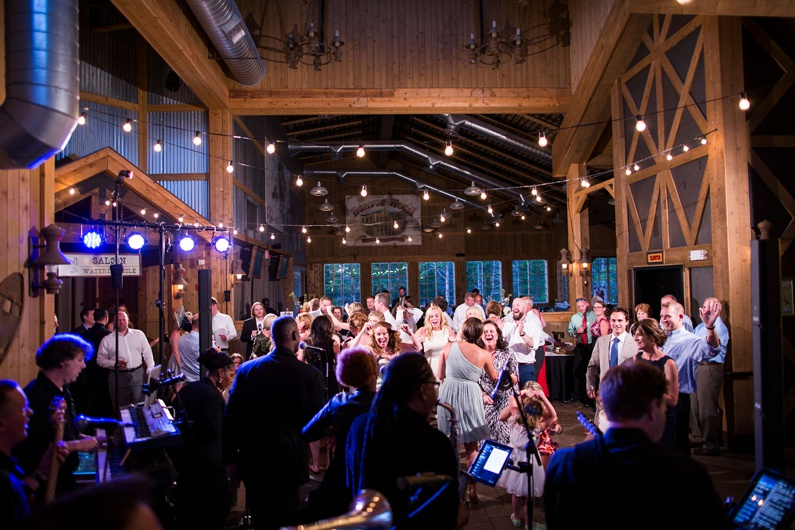 Guests on the dance floor as the band plays at mountain lodge wedding.