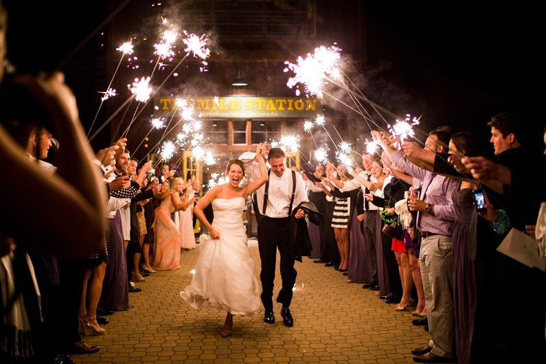 A wedding ends as a bride and groom exit their reception thru a tunnel of sparklers.