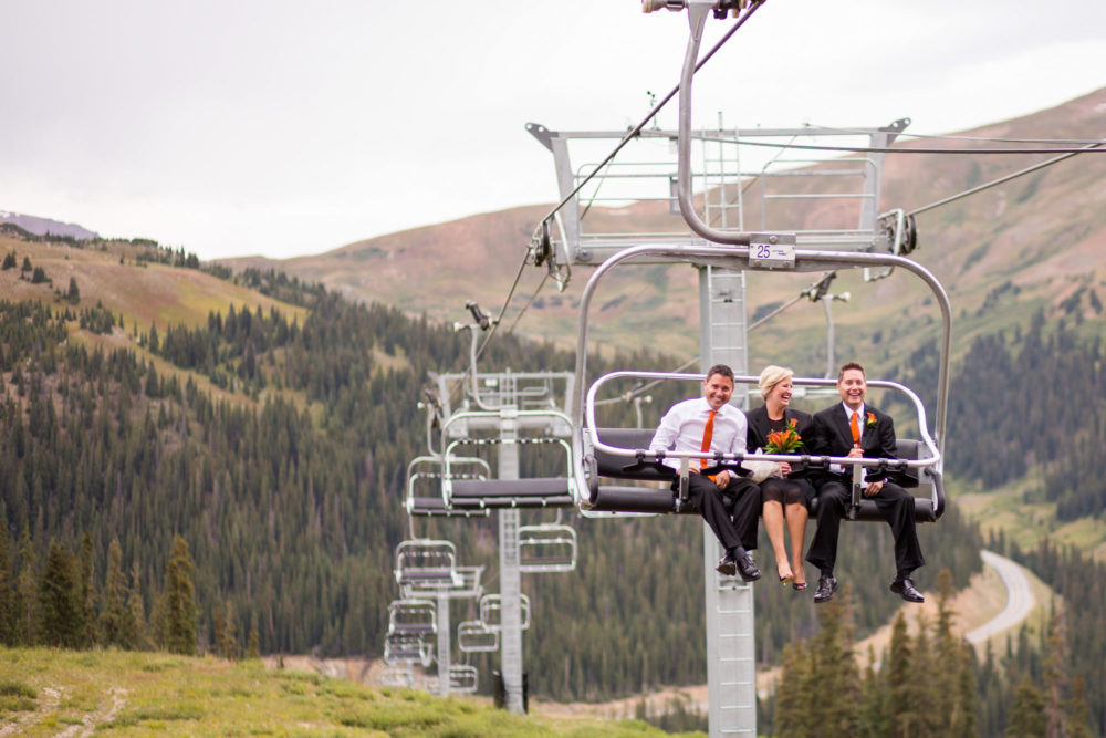 wedding guests riding chair lift to get to mountain wedding