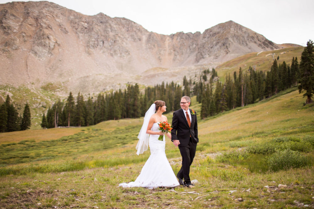 bride and groom holding hands with panoramic mountain views in background